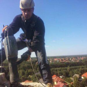 Alpinista przemysłowy w trakcie rozbiórki komina